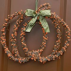 Fall Pumpkin wreath~ You can make this with 3 round wreaths, a berry garland and some ribbon.