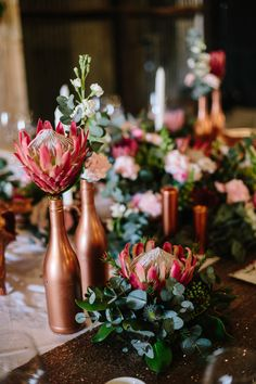 Wedding Flower Arrangements This Boho Wedding at The Cowshed Wowed with a Touch of Rock 'N' Roll - This wedding at the Cowshed was bohemian chic with blue, cranberry, and rose gold accents, a DIY macrame ceremony backdrop, and protea flower arrangements. Wedding Flower Arrangements, Wedding Table Centerpieces, Wedding Reception Decorations, Flower Centerpieces, Floral Arrangements, Wedding Ideas, Protea Centerpiece, Centerpiece Ideas, Wedding Ceremony