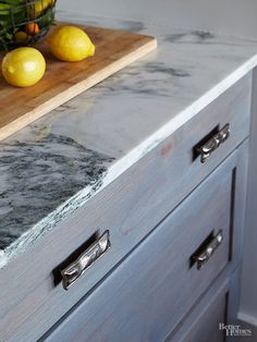 Interplaying textures bring distinctive dimension to the small kitchen. Distressed pewter pulls and a cabinet finish that lets the wood grain show through pick up on the colors of polished-marble countertops. The mix of shiny and matte finishes is a simple solution to add visual interest.