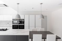 Nolte handleless kitchen in white and grey with Dekton Worksurfaces and siemens appliances.