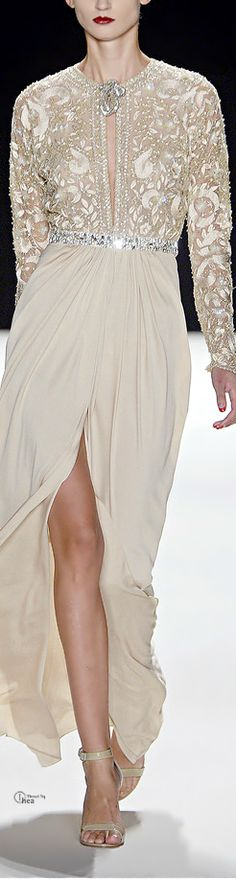 A great white split skirt, with a jumper-style torso covered in golden embroidery with a great plunging cut-out and brooch adornment.