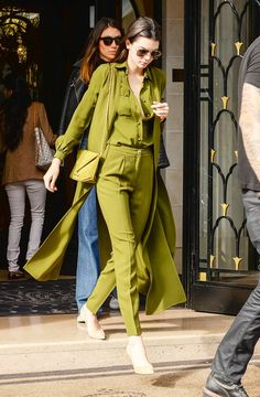 Kendall Jenner wears an olive green button-down shirt, trousers, and duster with a matching bag and nude heels