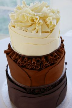 Tiered chocolate cake, each tier a different type of chocolate. Topped with large chocolate curled.