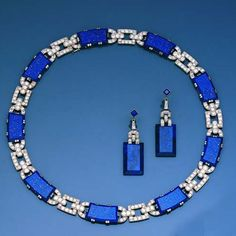 An art deco lapis lazuli and diamond demi-parure, circa 1930  The collar necklace composed of a series of curved rectangular and semi-circular shaped links, each millegrain-set with old brilliant-cut diamonds, set alternately with bevelled rectangular lapis lazuli plaques, to a concealed clasp, with a pair of pendent earrings and bracelet en suite, diamonds approximately 16.5 carats total, length of collar necklace 37.0cm., length of bracelet 18.0cm., length of earrings 5.4cm.