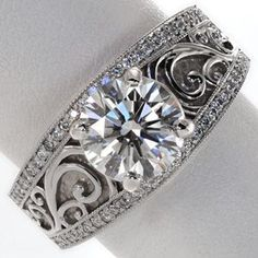 Design 2178 - This stunning ring features a 2.00 carat round brilliant center diamond on a wide, antique inspired band. The edges are detailed with micro pavé and milgrain texturing while the middle is adorned with large, graceful filigree curls. The band gracefully tapers down towards the bottom for comfort.