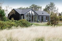 wonderful bushes surrounding the gorgeous black wooden house with glass window and stunning perenials