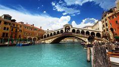 【リアルト橋】  「白い巨象」の異名をもつリアルト橋(Ponte di Rialto)は、カナル・グランデにかかる橋です。ヴェネツィアは地形的に水害に悩まされやすい土地ですが、リアルト橋周辺は比較的海抜が高かったため、最も初期から街の中心として栄えてきました。 「へ」の字型をしているのが特徴の石造りの橋です。
