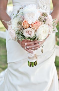 Pretty peach and white wedding bouquet, plus a locket with pictures of grandparents who couldn't be at the ceremony.