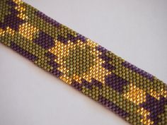 SALE was $62 now $56 here is a carefully hand-woven beadwork bracelet i made using Delica seed beads in matte olive green, translucent plum, and crystal cut, 24k gold lined. with lots of experimentation i fashioned this pattern off a piece of elastic trim i liked whose mass manufacturer