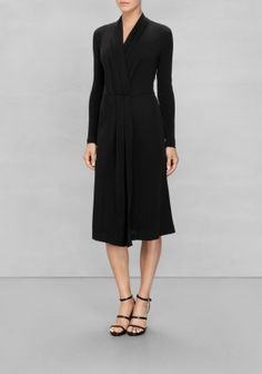 Understated and demure, this long-sleeve dress is crafted from weighty viscose that drapes gracefully at front where cross-over pleats create a shawl collar and a swingy skirt.