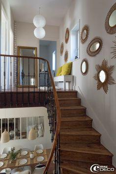 La cage d'escalier de la maison de Florence Bouvier est décorée d'une collection de miroirs soleil en rotin vintage chinés aux Puces du Cana...