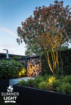 In de reeks SUMMER LIGHTS deze sfeervolle tuin met daarin een buitendouche en buitenspot MINI SCOPE die de grote struik uit licht.