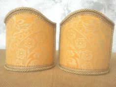 Couple of lampshades decorated with damask fabric with floreal patterns in high relief, finished with gold trimmings. € 34,00