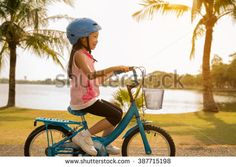 Asian girls cycling at the park in the morning. - stock photo