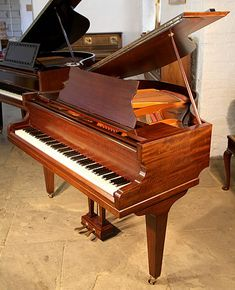 A 1932, Broadwood baby grand piano with a fiddleback mahogany case and square tapered legs