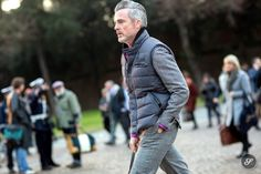 men wearing a puffy vest and a suit on a street style photo taken at Pitti Uomo