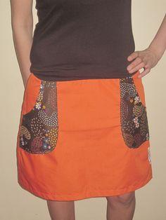 Falda naranja (tela sintética y algodón), cintura elástica.