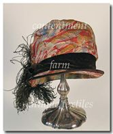 1920s Flapper Cloche, made of a colorful lamé fabric and the crown is wrapped with brown velvet and adorned at the side with a brown ostrich feather.