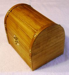 "Beautiful wooden hand stained treasure chest box with gold accented hinges and clasp. The box is hand stained with golden oak and sealed with a coat of polyurethane. The outside is approximately 6 1/8L x 4 3/8W x 4 7/8""H, and the inside is approximately 5 1/2L x 3 5/8W x 2 1/8""H. The inside is lined with black felt.  Thanks for looking and have a great day."
