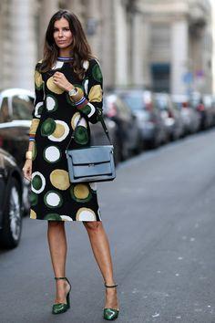 Posando en la carretera con un 'look' en tonos verdes, desde el vestido estampado con topos grandes, zapatos de pulsera y punta y bolsito.