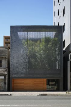 This beautifully serene house, built in downtown Hiroshima by Hiroshi Nakamura/NAP, features an optical glass facade to let in light and air, an interior pond, and a garden and soaring trees, which are visible from every room. The house is tucked into a space between two large residential buildings as well as some shops. Natural wood and earth tones are used throughout the home to create a natural, peaceful oasis.