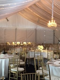 ambient lighting under white frame tent with black chiavari chair