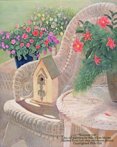 """""""Summer Joy"""", an oil painting by Nancy Lee Moran, has bright flowers of impatiens, violas, and mandevilla.  A birdhouse sits on a wicker chair. Painted from her own reference photos, copyrighted 2014 USA, the oil painting is for art licensing, Romantic Realism in colors of violet, coral red, yellow, and fuchsia pink."""