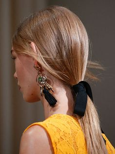 """The chicest hair accessory we saw on the spring runways was also the simplest—a plain black ribbon. Tied around the base of low ponytails at Oscar de la Renta, it looked soft, romantic, and effortless, in part because of how the ribbon was tied. """"It's not a perfect bow—it's more like a half bow so one side kind of falls,"""" said hairstylist Guido. """"It makes it so the style doesn't become too precious."""""""