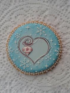 Ornament in heart surrounded by delicate snowflakes & lace piping on airbrushed blue background