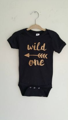 This listing is for design Wild One on a deluxe bodysuit with gold glitter print  Items are printed with commercial grade vinyl and professionally pressed. Bodysuits: Brand - Laughing Giraffe •Baby Short Sleeve Crew Neck T-Shirt •Interlock Knit, 7.2 Oz. 100% Cotton * Wash inside out and hang dry for longest life, when ironing iron around the design  Items are made to order in a smoke-free and pet-free home  Shipping is always USPS Priority which means delivery will only take 1-3 days…