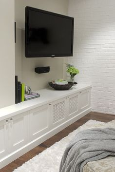 Style notes: A wall-mounted TV and a long, low cabinet give this space its sleek, modern look. Fresh white paint, wood-look floors and a fluffy rug, as seen here, may turn your own basement into your favorite room in the house.