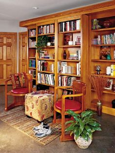 The center bookcases are attached to a track with wheels.  They move apart to reveal a murphy bed.  From Southern Living.
