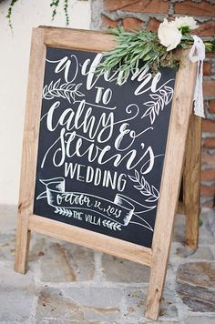 A rustic-chic chalkboard greets guests to Cathy and Steven's wedding in impeccable calligraphy.