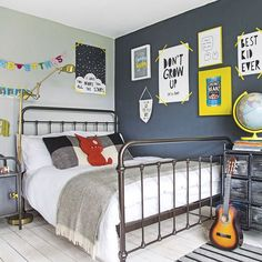 Modern children's room with colourful wall art. Add quirky artwork to a dark wall to create your own picture gallery that stands out. Neutral shades paired with a dark navy blue create a moody feature wall perfect for an adolescent's room. Industrial-style furniture looks the part next to the darker shade, while yellow accessories perk up the space with a fun, bright tone. Washi tape for artwork looks relaxed and is practical for swapping and changing pictures.