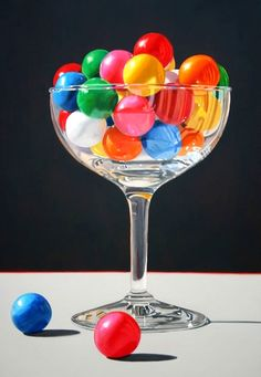 Rainbow colored gumballs in a clear wine glass.