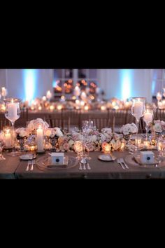 top table idea lots of candles and a rolling flower arrangment with little pots of flowers to break it up??