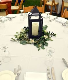Vintage lantern wedding centerpiece surrounded by white alstromeria, seeded eucalyptus and olive branch. Flowers by Chester's Flowers in Utica NY and wedding located at Harding Farm in Clinton, NY.
