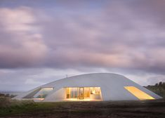 This zinc-clad house in Australia by Sydney architect James Stockwell has a sand dune-shaped body that turns its back to the prevailing wind