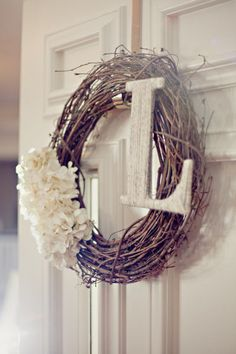 Style Me Pretty - grapevine wreath with soft white flowers and a whitewashed initial