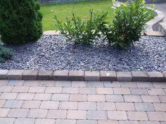 Rådhus brunmix belegningsstein og kantstein med Arctic Brown Slate Dekorstein i blomsterbedet.