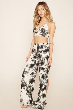 A pair of woven pants by R by Raga™ with an allover tie-dye print, high side slits, a wide-leg silhouette, and a concealed back zipper. Matching crop top available.
