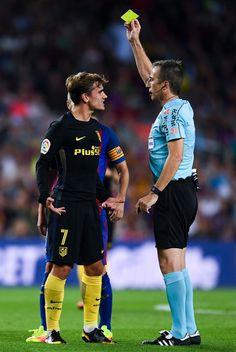 Antoine Griezmann of Club Atletico de Madrid is shown a yellow card by the referee David Fernandez Borbalan after a challlenge on Ardan Turan of FC Barcelona, not in picture, during the La Liga match between FC Barcelona and Club Atletico de Madrid at the Camp Nou stadium on September 21, 2016 in Barcelona, Catalonia.