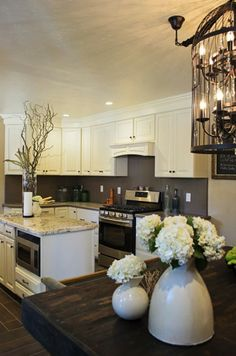 White cabinets and stainless steel appliances are a must in this modern kitchen. #DreamBuilders