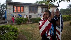 Ein Mann steht umhüllt mit einer US-Flagge am Straßenrand
