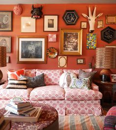 This amazing gallery wall includes many unique objects that aren't custom framed art, set on a bold terra cotta wall. Taking this grouping to the ceiling allows for some uniquely situated pieces making a statement, which perfectly details the owner's personality. And it's something we can certainly appreciate!