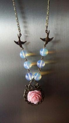 Collar en bronce con aves, opalo y rosa de resina en el centro
