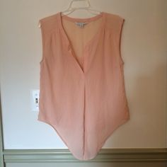 Blouse from American Eagle Cute sleeveless top from American Eagle. Cut down the middle in the front so it can be tied into a knot at the bottom, or stay as an open flap! Light pink color American Eagle Outfitters Tops Blouses