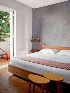 O quarto do casal se abre para a varanda, presenteada com a sombra das árvores. A parede de efeito manchado é obra do Adriana e Carlota Atelier de Pinturas. Lá fora, a mangueira refresca a varanda.