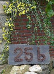 hausnummer aus bindedraht auf altem holzbrett