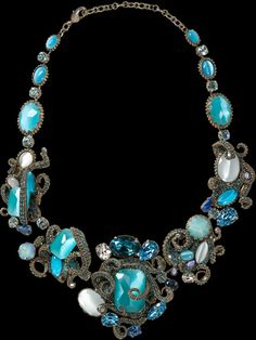 "Aquatic Bib Necklace    Be prepared to be the center of attention when you wear the Aquatic Bib Necklace to your next event. Eyes will be drawn to the stunning detail of chain rhinestone wrapping around dazzling shades of blue, created by Swarovski crystal and you will sparkle like the sea.    Item NumberNSP3ASAQU width 2½"" length 15""  $1844"